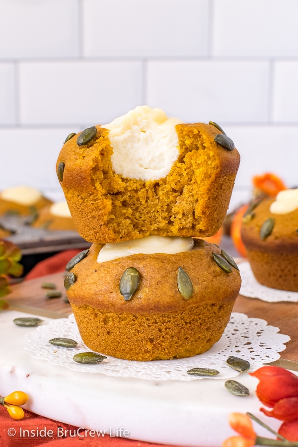 Two pumpkin cream cheese muffins stacked on top of each other and a bite taken out of the top muffin showing the center