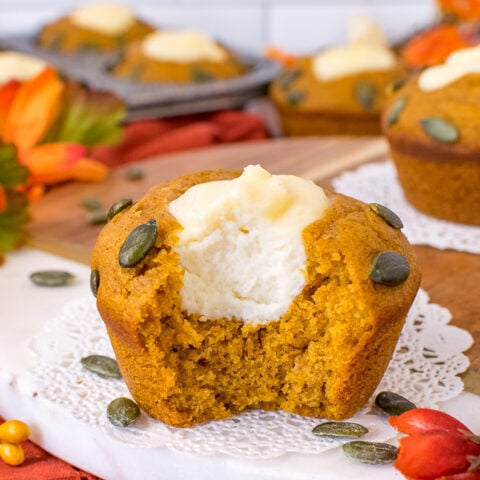 A pumpkin cream cheese muffin on a tray with a bite taken out showing the center