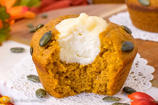 A pumpkin cheesecake muffin with a bite take out of it showing the creamy center