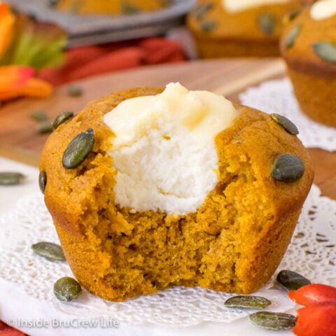 A pumpkin cream cheese muffin on a white doily with a bite taken out of it showing the filling center