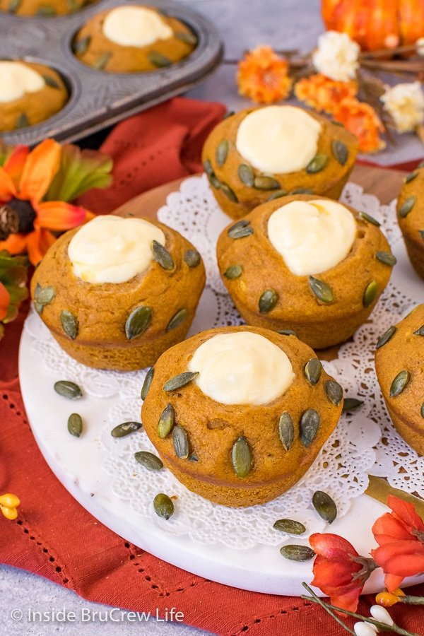 A tray of pumpkin cream cheese muffins with pepitas on top