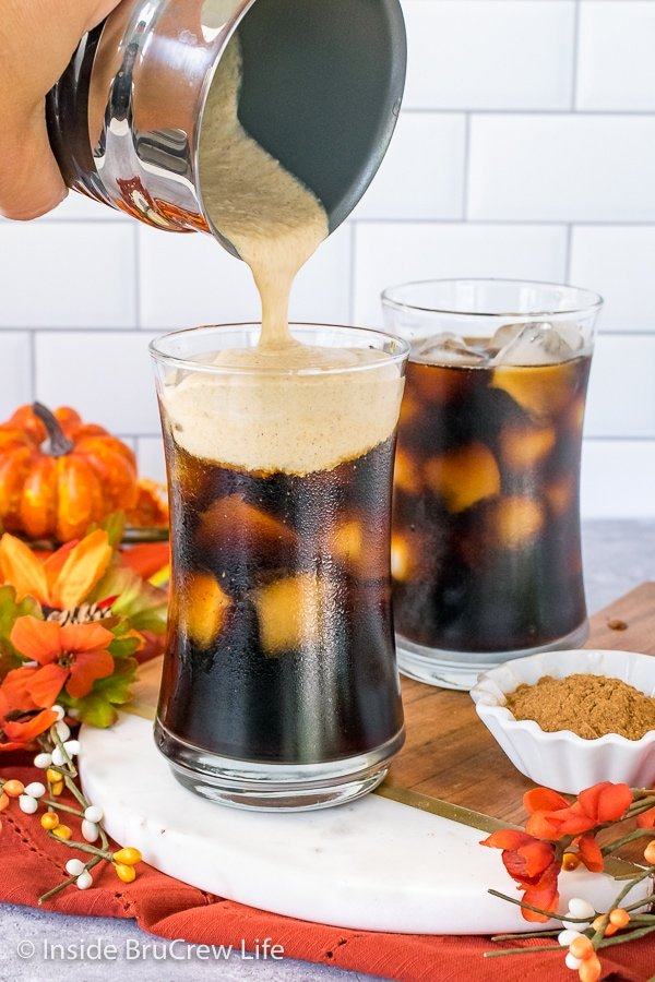 Two cups of iced cold brew on a tray with a jar of pumpkin cream foam being poured into the front cup