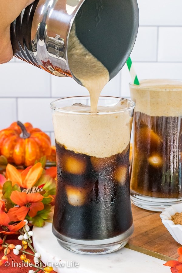 A glass of iced cold brew coffee with pumpkin cream cold foam being poured on top