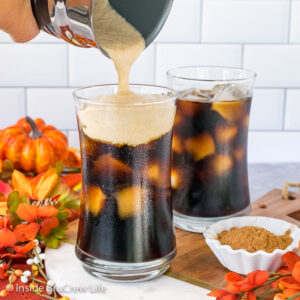 Two glasses of iced pumpkin cream cold brew on a tray with pumpkin cold foam being poured into the front glass