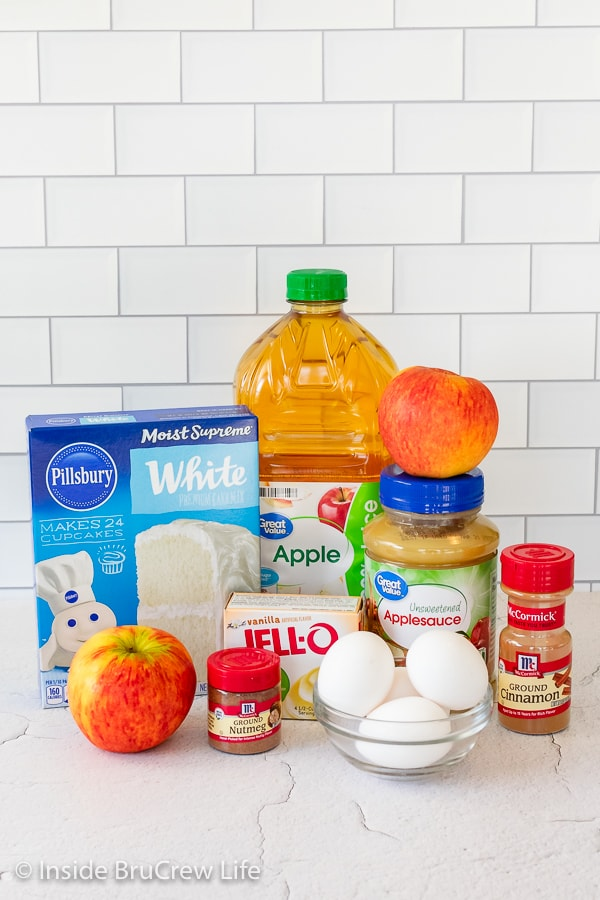 Ingredients needed to make a cinnamon apple cake on a white board.