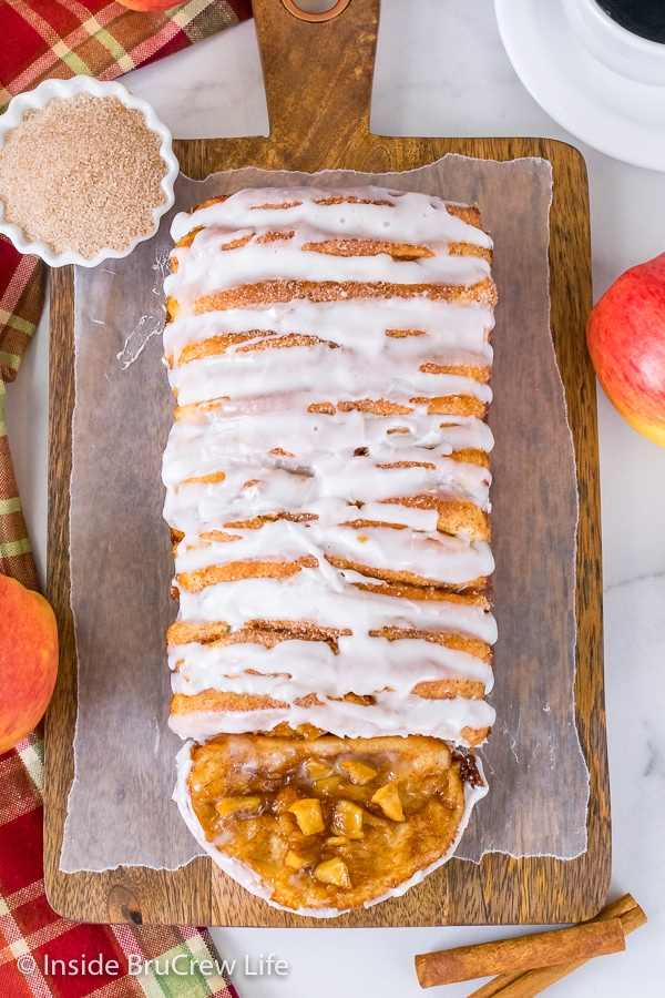 Overhead picture of a wood tray with a loaf of apple cinnamon pull apart bread drizzled with glaze
