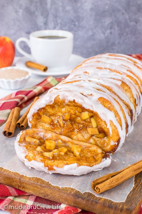 A wood board with a loaf of apple cinnamon pull apart bread drizzled with glaze and one sliced falling forward