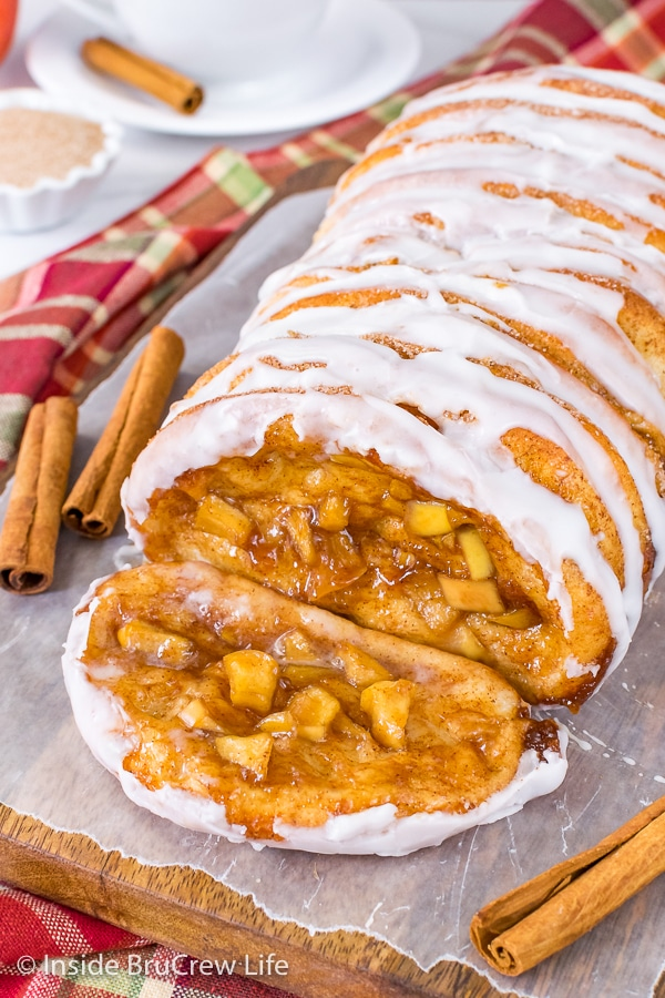 A slice of apple cinnamon pull apart bread lying on a wood board with the rest of the loaf behind it