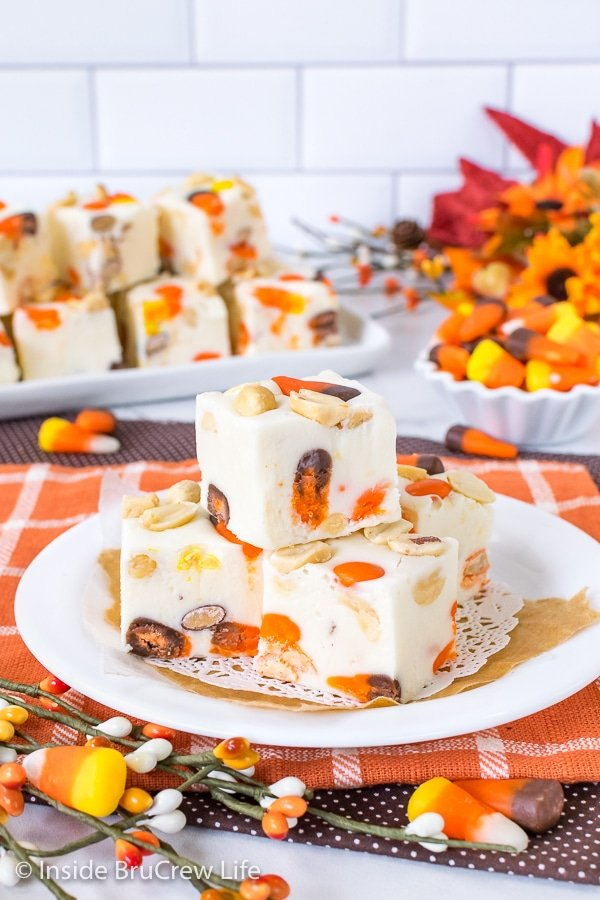 An orange towel with a white plate on it with squares of candy corn fudge stacked on it