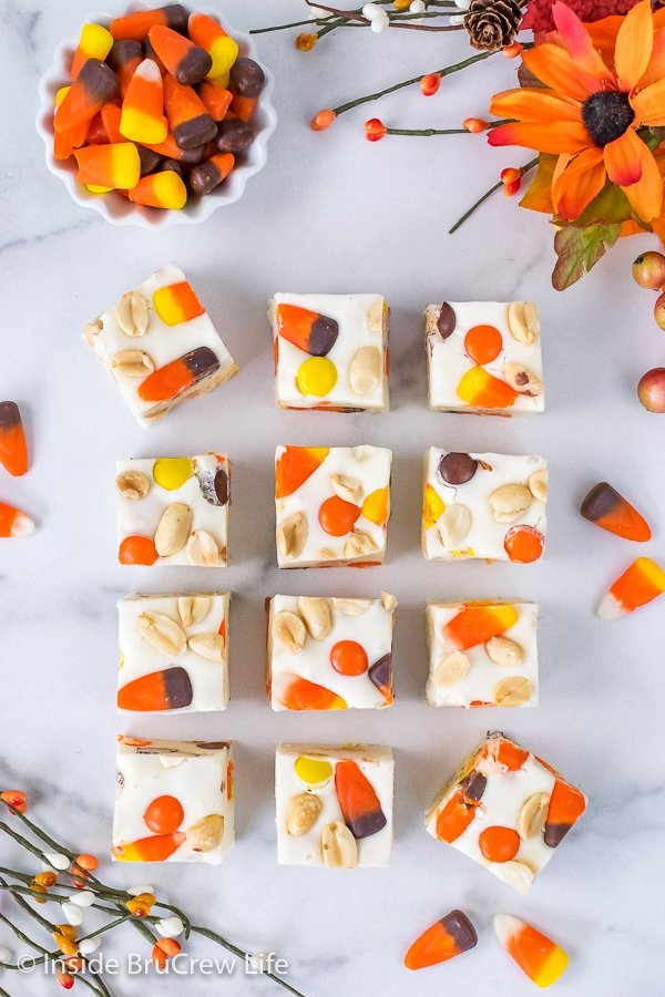 Overhead picture of squares of candy corn fudge on a white marble background