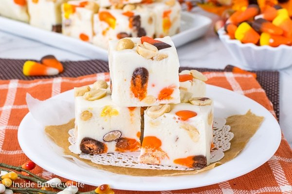A white plate on an orange towel with three squares of candy corn fudge stacked on it and more fudge behind it