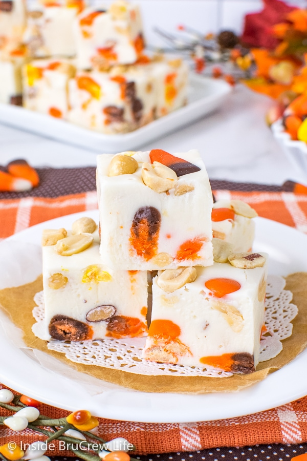 A white plate on an orange towel with squares of candy corn fudge on it and more behind it