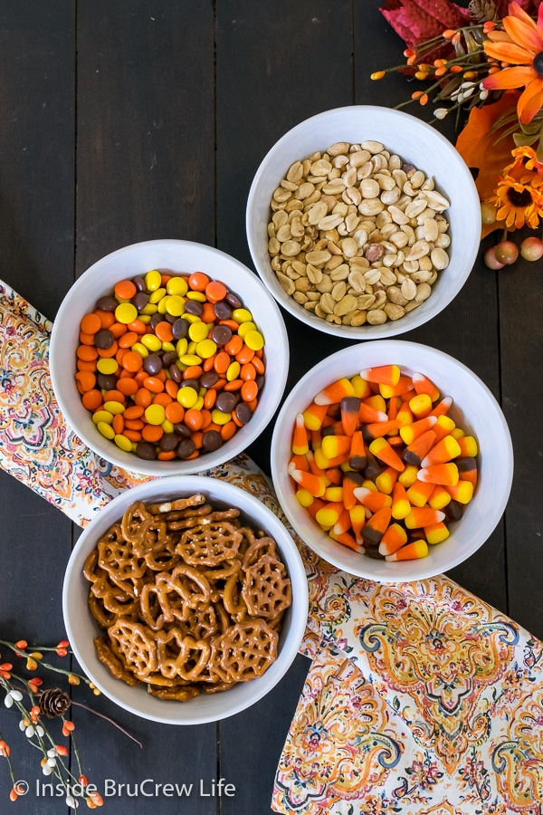 Four white bowls filled with the ingredients for candy corn snack mix