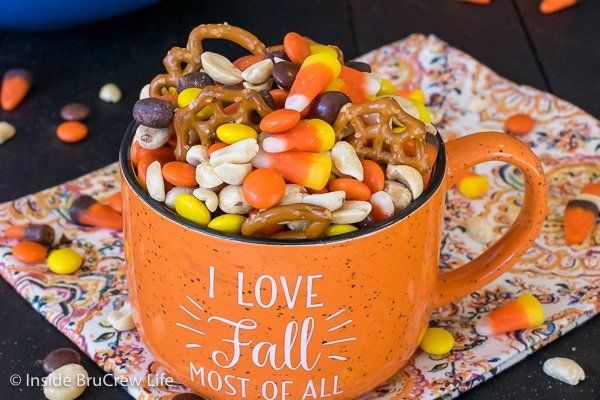 An orange fall mug filled with candy corn snack mix
