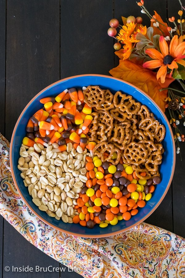 A blue bowl filled with the ingredients for candy corn snack mix