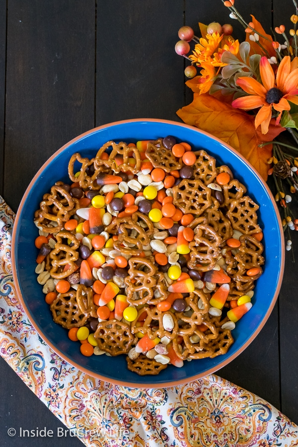 An overhead picture of a blue bowl filled with candy corn snack mix