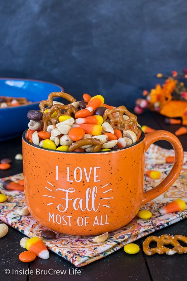 An orange fall mug on a dark background filled with candy corn snack mix