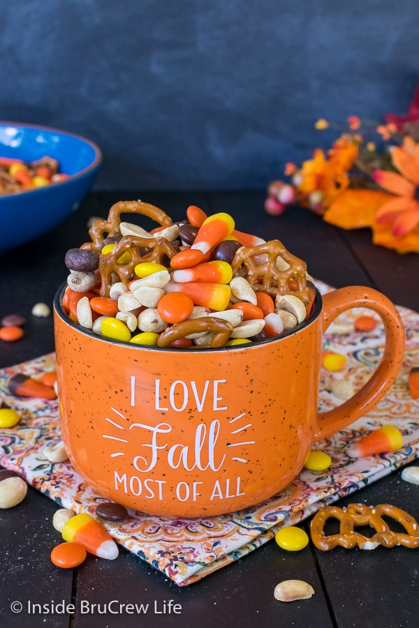 An orange fall mug filled with candy corn snack mix with a bowl of mix behind it