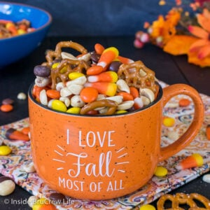 An orange mug filled with candy corn snack mix