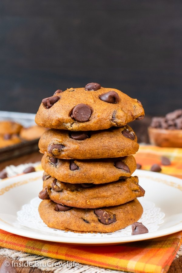 A white plate on an orange towel with a stack of pumpkin chocolate chip cookies.