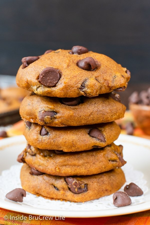 A stack of five pumpkin chocolate chip cookies on a white plate.