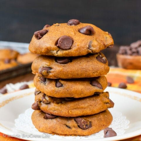 A stack of five chocolate chip pumpkin cookies on a white plate.