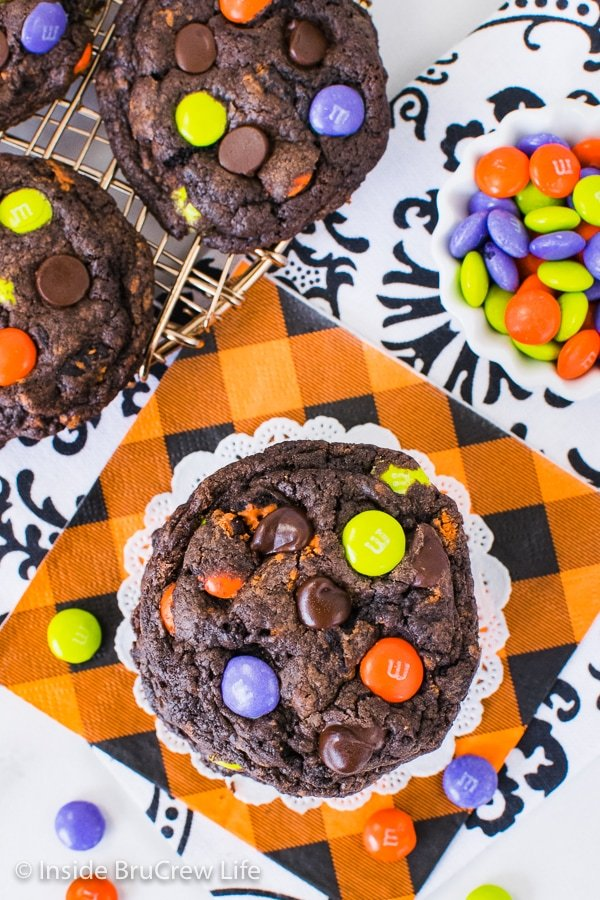 Overhead picture of a stack of Halloween Chocolate Cookies and Cream Cookies on an orange napkin with candies around it