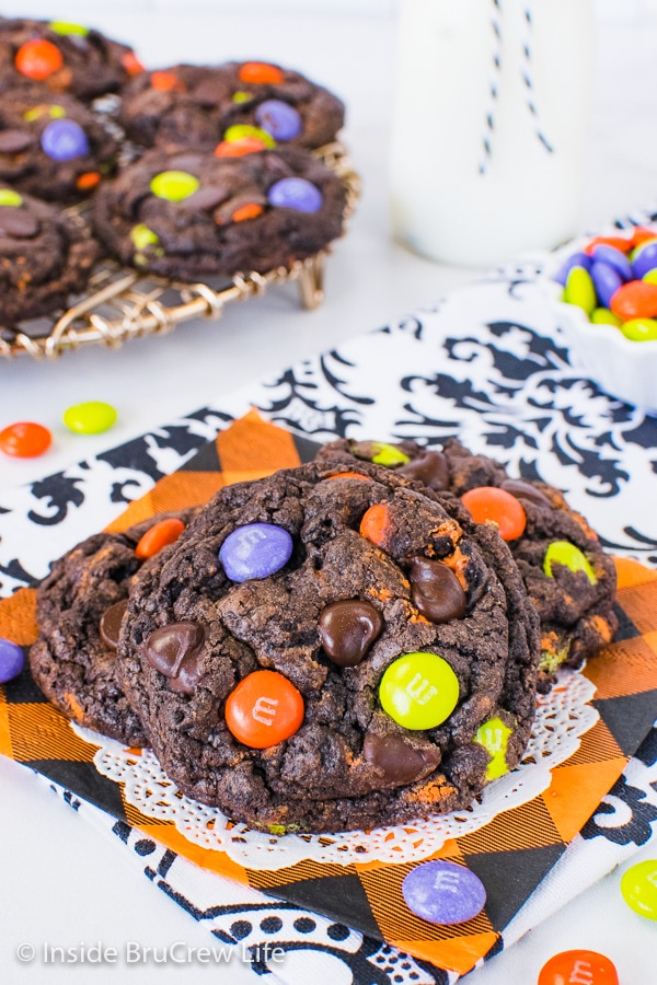 A close up of chocolate cookies and cream cookies topped with Halloween candies with more cookies behind it