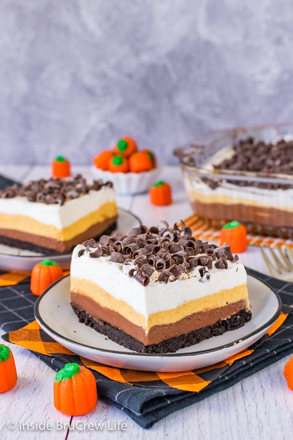 Two plates with pieces of chocolate pumpkin lasagna topped with chocolate curls on them