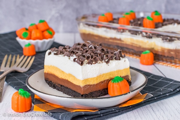 A square of chocolate pumpkin lasagna with chocolate curls on a white plate and the pan of dessert lasagna behind it