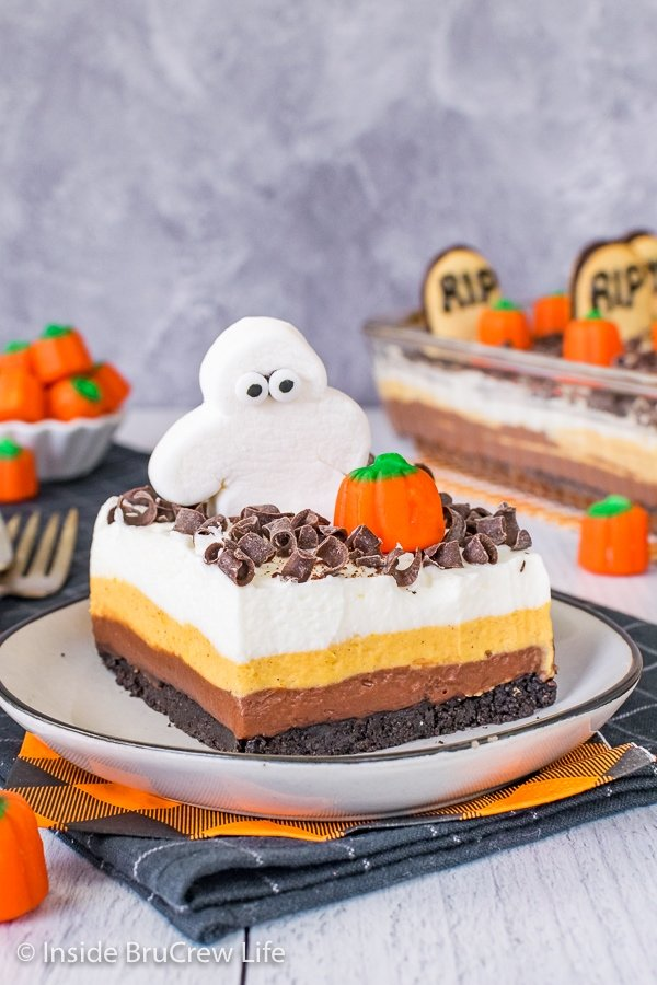 A white plate with a square of chocolate pumpkin lasagna topped with a marshmallow ghost and candy pumpkin