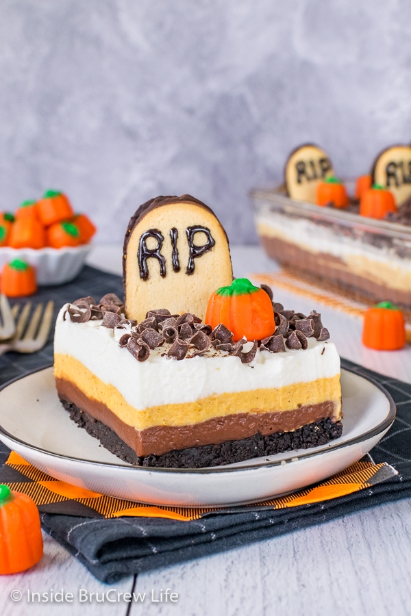 A white plate with a square of chocolate pumpkin lasagna topped with a tombstone cookie and candy pumpkin
