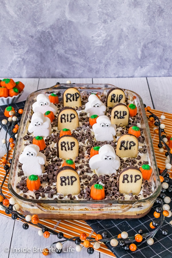 A pan of Chocolate Pumpkin Lasagna decorated with tombstone cookies, marshmallow ghosts, and candy pumpkins
