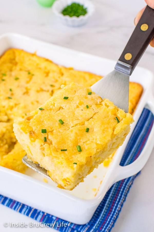 A spatula lifting a square of Jiffy corn casserole up and out of a white casserole dish