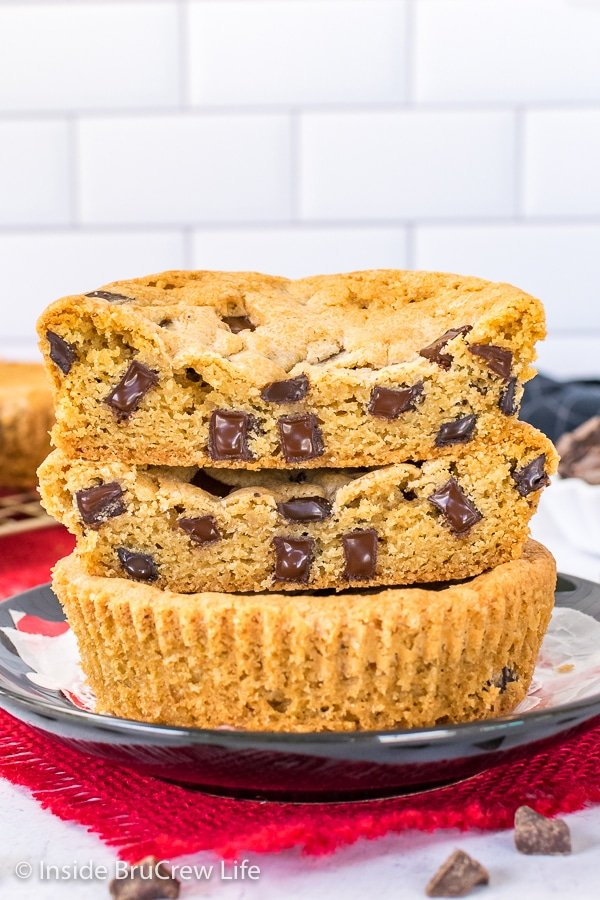 A deep dish chocolate chip cookie cut in half and stacked together showing the melty chunks in the Num Num cookies