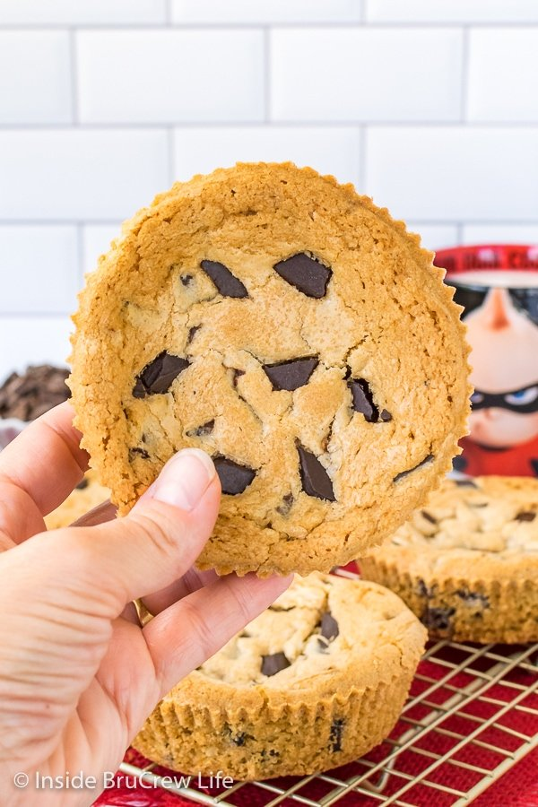 A giant Jack Jack Num Num cookie with chocolate chunks on top held up in front of a white background