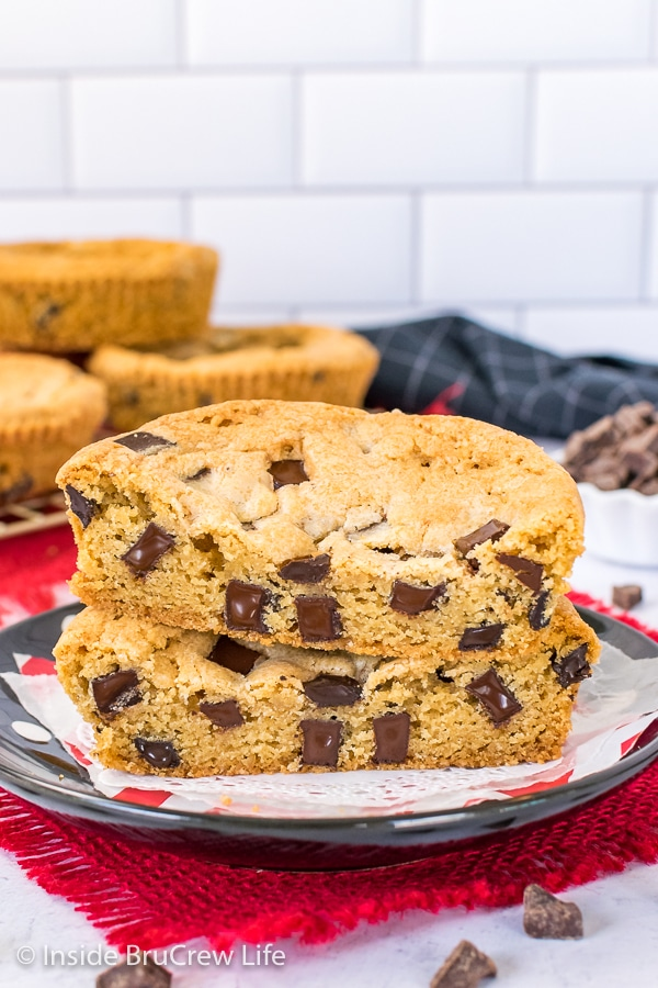 A chocolate chunk Num Num cookie cut in half and stacked on a black plate showing the melty chunks inside