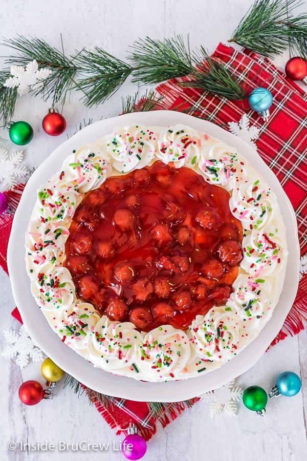 Overhead picture of a cherry mousse brownie cake topped with cherry pie filling and whipped cream swirls