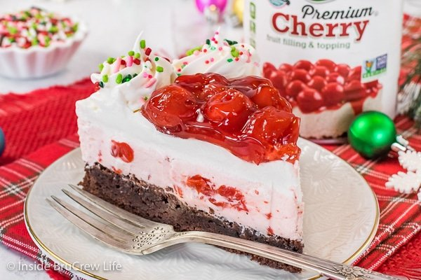 A slice of cherry mousse brownie cake on a white plate with a can of cherry pie filling behind it