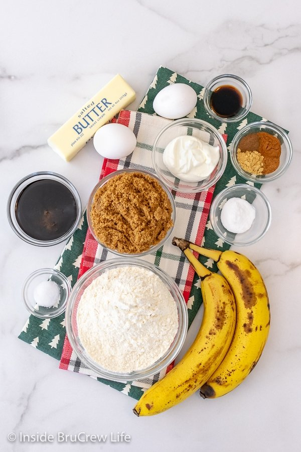 A white background with bowls of ingredients to make gingerbread banana bread