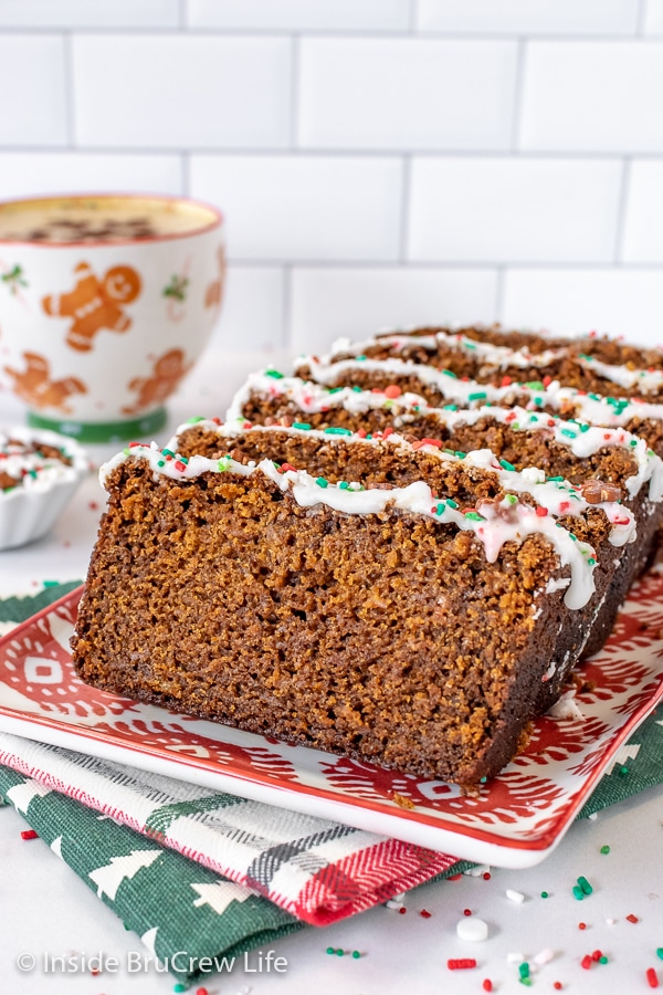 A red and white plate with slices of gingerbread banana bread standing on it and a cup of coffee behind it