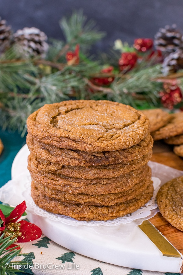 A stack of molasses crackle cookies on a white and brown tray with greenery behind it