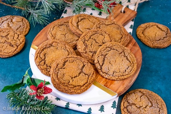 Overhead picture of a round tray with molasses crackle cookies stacked and scattered on it