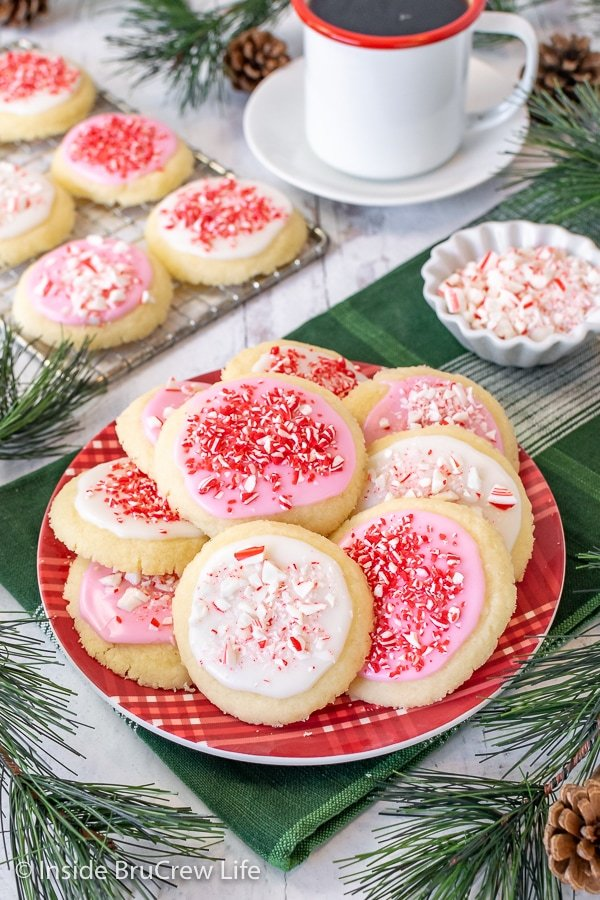 A red plate on a green towel with peppermint meltaway cookies topped with white and pink glaze and peppermint candies
