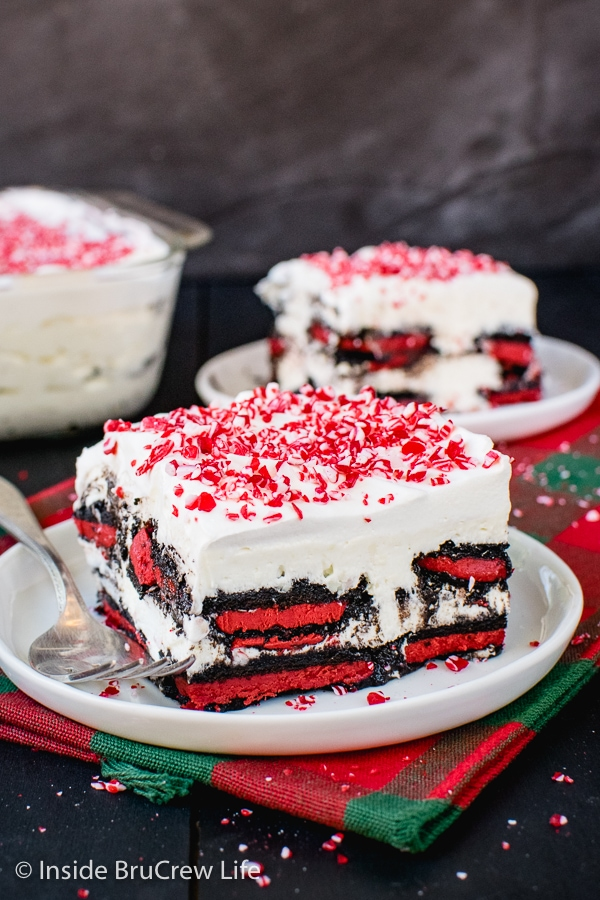 Two white plates on a holiday towel with squares of peppermint oreo icebox cake topped with crushed peppermint bits on top