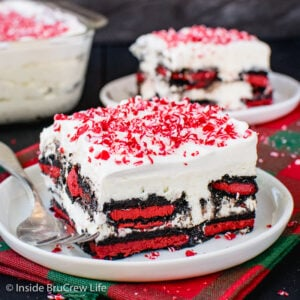 Two white plates with squares of peppermint oreo icebox cake topped with crushed peppermint candies