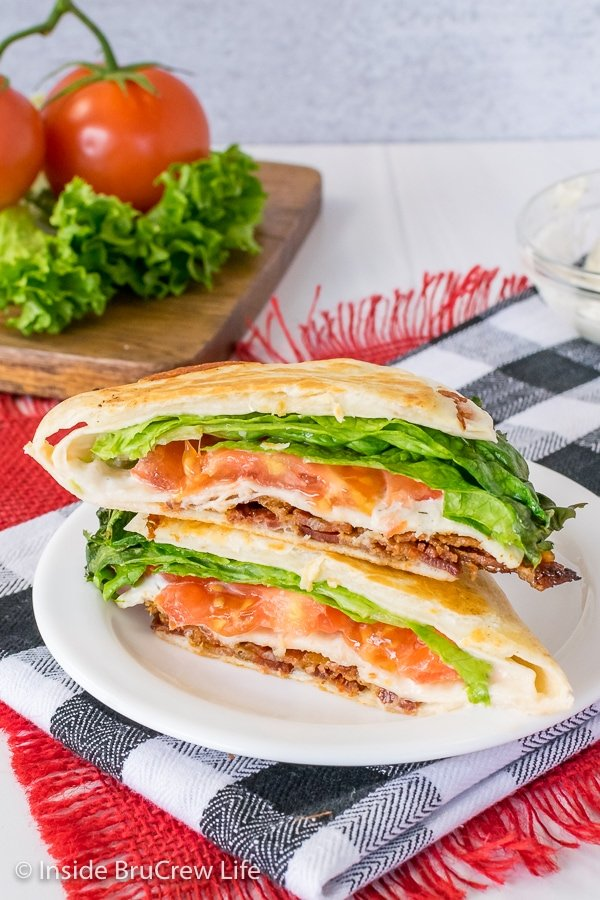 A BLT tortilla wrap hack cut in half and stacked on a white plate showing the inside fillings