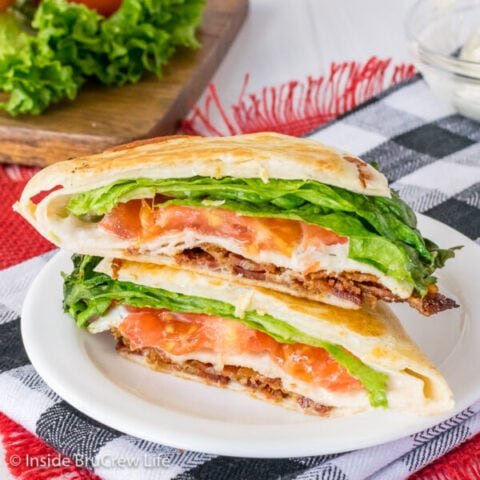 A white plate with two halves of a blt tortilla wrap hack stacked on top of it showing the fillings