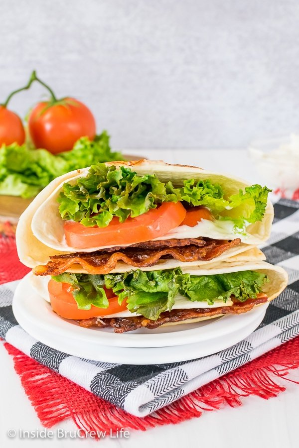Two BLT tortilla wraps cooked and stacked on top of each other on a white plate