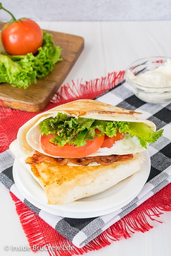 Two BLT tortilla wrap hacks stacked on top of each other on a white plate